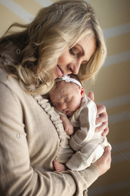 Mother happily holds newborn daughter close to her chest at home