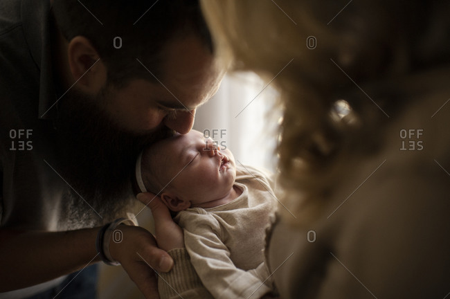 Father kissing sleeping newborn daughters head in mother's arms