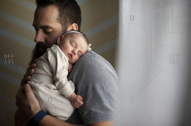 Father embracing sleeping newborn daughter on shoulder at home