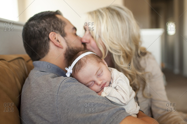 Close up of newborn baby sleeping with parents kissing in background