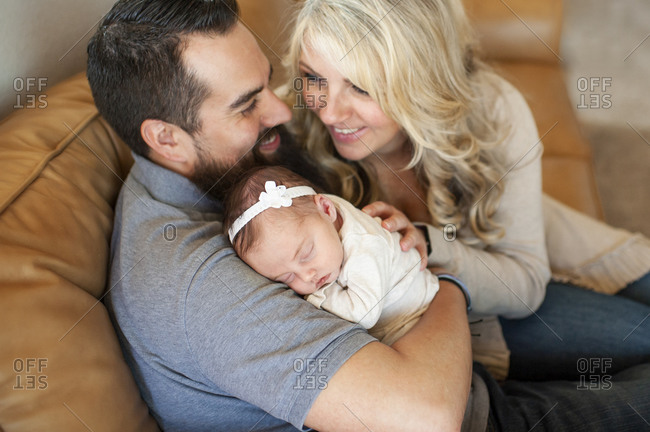 Happy smiling family holding newborn baby girl at home on couch