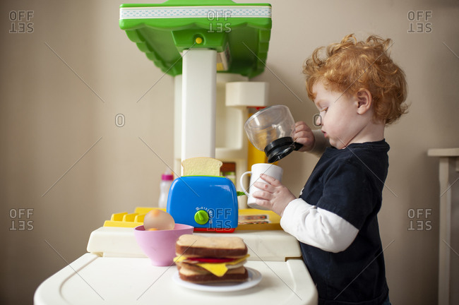Toddler boy playing in toy kitchen pretending to pour coffee into cup