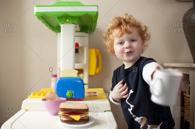 Toddler boy offering a cup of coffee in front of his play kitchen