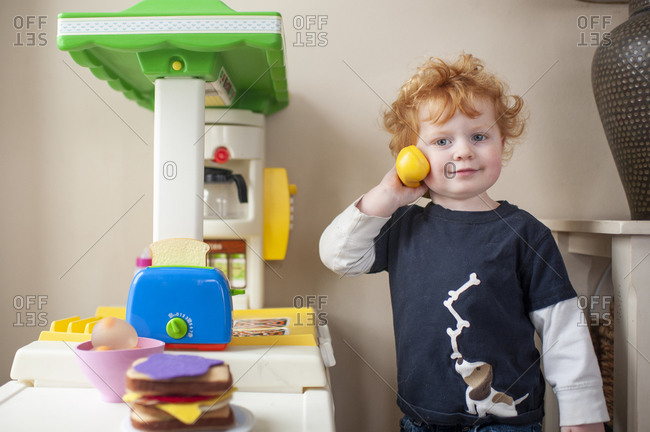 Toddler boy looking while answering phone in play kitchen at home
