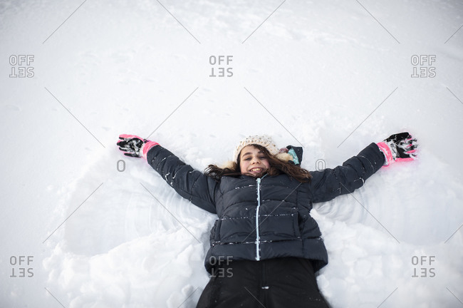 Girl smiling while making snow angel in the snow in front yard