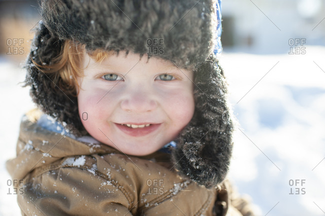 Up close of cute toddler in winter clothes and hat smiling in the snow
