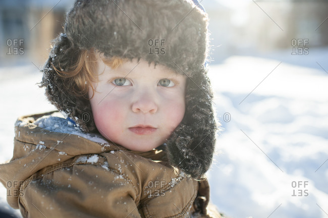 Portrait of toddler boy in winter clothes and hat out in the snow