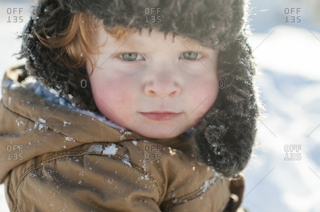 Toddler making serious face in winter hat and jacket in the snow