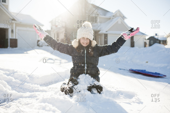 Girl 10-12 years old having fun in the snow in front of house