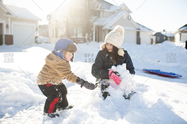 Brother and sister play in the snow together in front of house