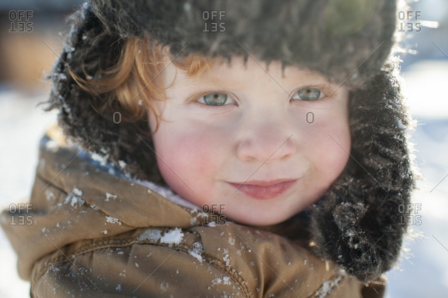 Portrait of happy smiling toddler bundled up in winter hat in jacket