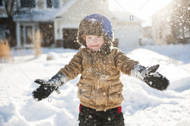 Toddler boy playing and smiling while throwing snow in front of house