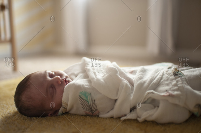 Newborn baby girl wrapped up in blanket sleeping at home