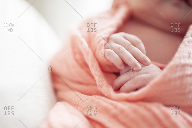 Close up of newborn baby girls hands wrapped in pink blanket