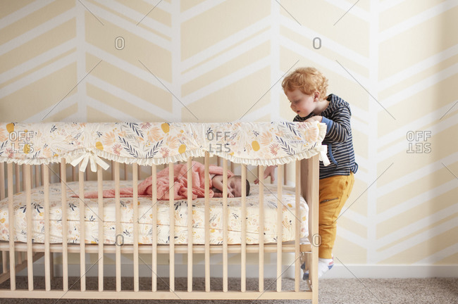 Toddler reaching in crib trying to touch newborn baby's head