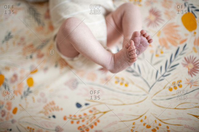 Close up of newborn feet against floral crib sheet at home