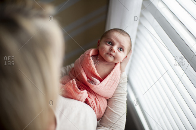 Above view of mother holding newborn daughter looking up at window