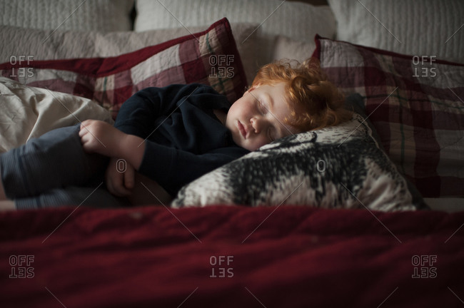 Toddler boy 1-2 years old asleep on pillows in bed with red bedding