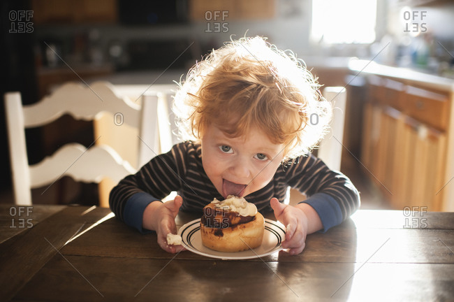 Toddler boy sitting at table licking a cinnamon roll at home