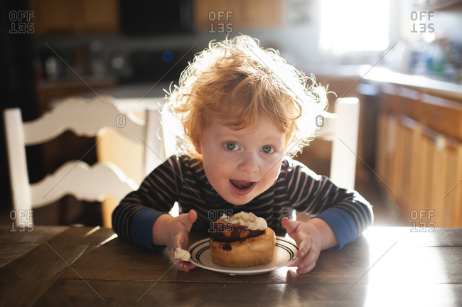 Toddler boy sitting at table enjoying a cinnamon roll at home