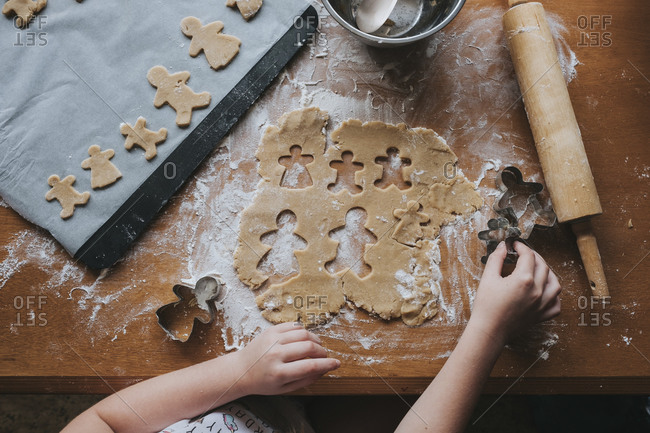 Looking down at young girl holding onto gingerbread cutter