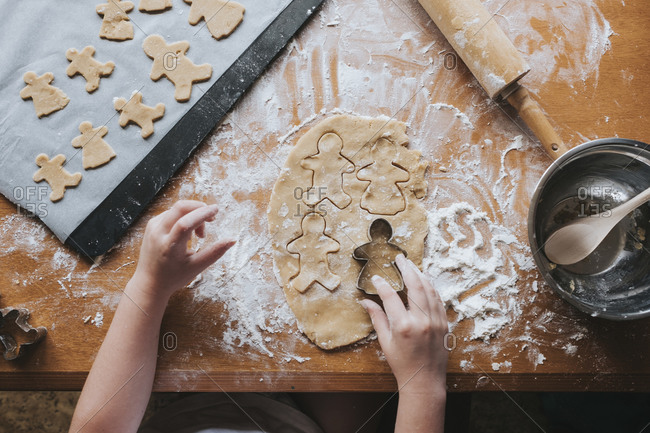 Looking down at young girl cutting our gingerbread man