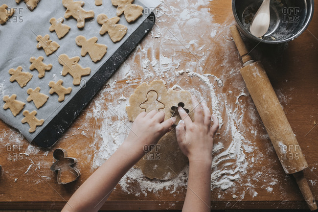 Looking down at young girl using cutters on gingerbread dough