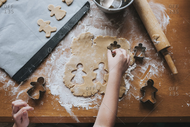 Young girl cutting our gingerbread man from dough using cutters