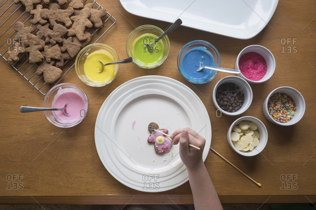 Young girl decorating gingerbread with frosting