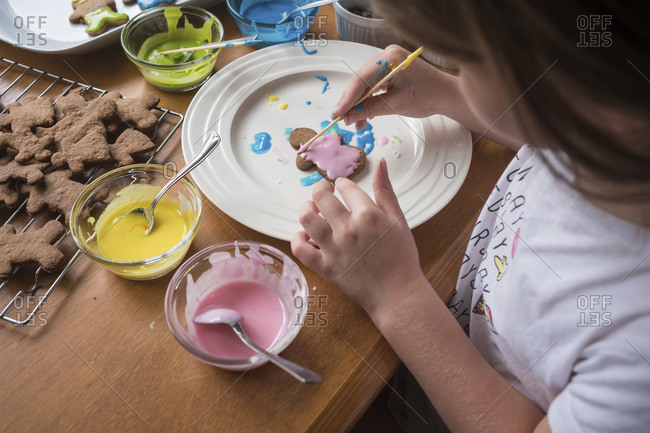 Looking down at young girl decorating gingerbread with frosting