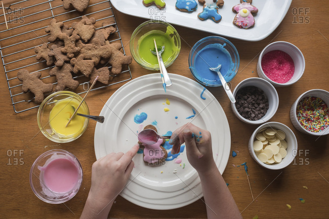Young girl decorating gingerbread with frosting on a plate