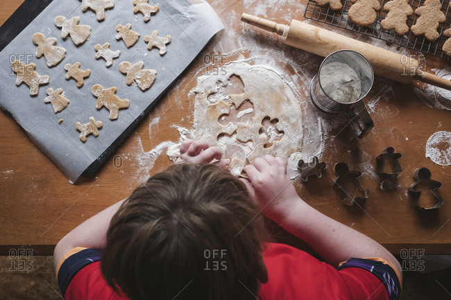 Looking down at boy cutting out gingerbread from dough