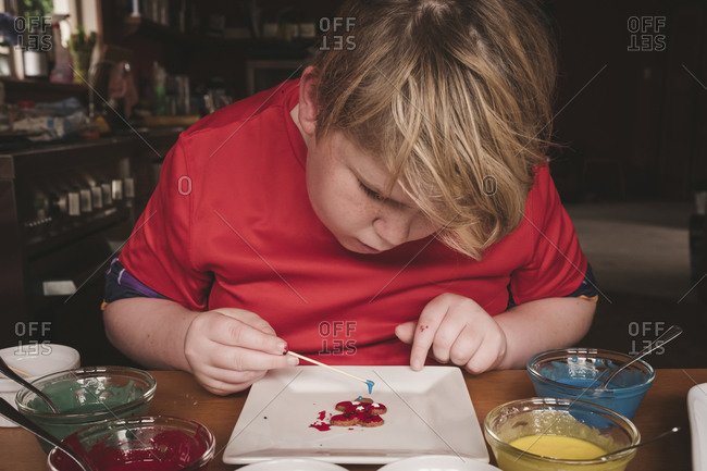 Boy decorating gingerbread with frosting and tooth pick