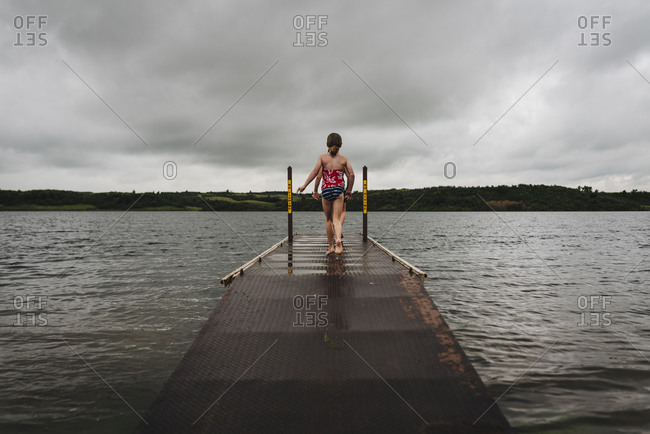Little Girls Walk on Dock Toward Water on a Cloudy Day at the Lake