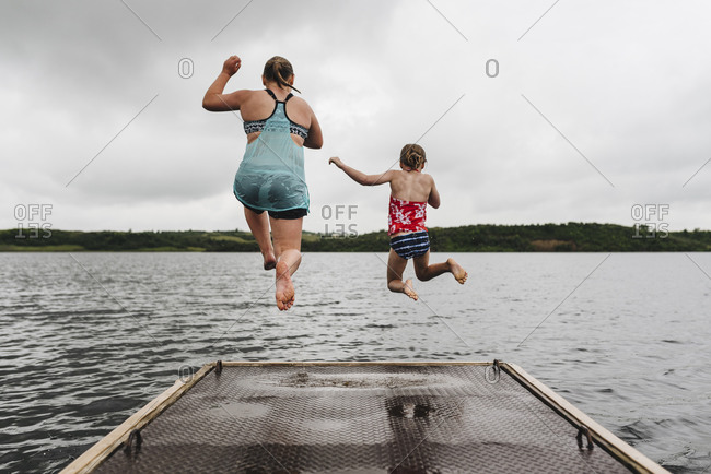 Little Girls Jump off Dock into Lake on a Cloudy Summer Day
