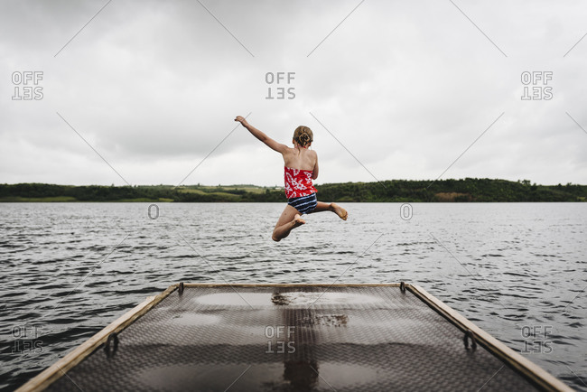 Little Girl Jumps off Dock into Lake on a Cloudy Summer Day