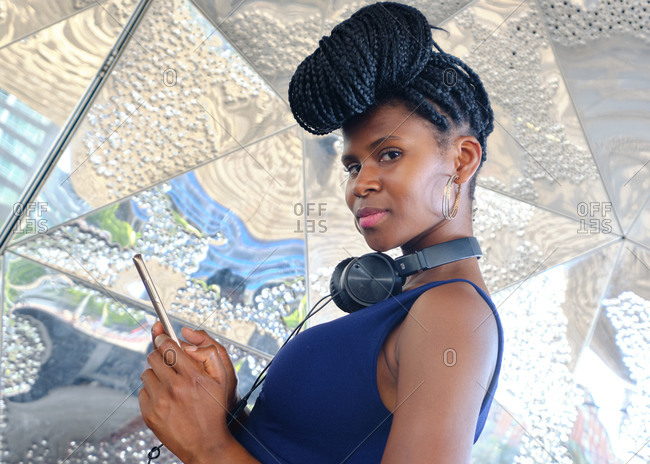young black woman with very long braids and very attractive and sensual enjoying barcelona in summer and doing model with mobile, glasses and camera, technology concept. Barcelona, Spain