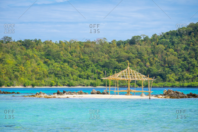 Bamboo structure on beach surrounded by blue water, Coron, Philippines