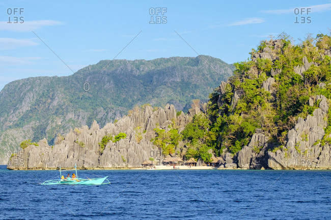 Philippines, MIMAROPA, Coron - December 22, 2014: Outrigger boat passes village on Coron Island, Philippines