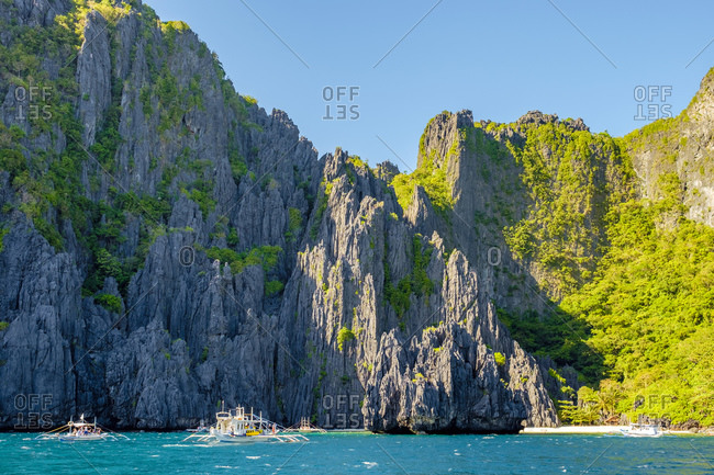 Philippines, MIMAROPA, El Nido - December 27, 2014: Dramatic karst limestone cliffs at Secret Lagoon Beach on Miniloc Island
