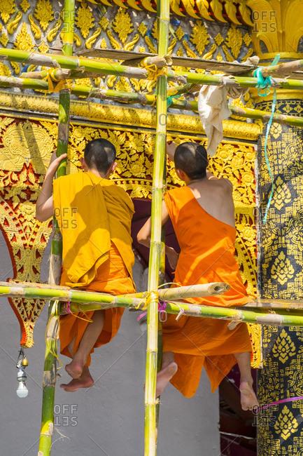 Buddhist novice monks painting temple facade, Luang Prabang