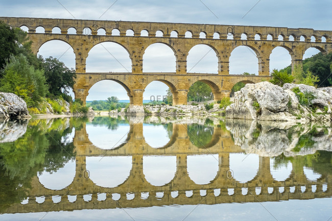 Pont du Gard reflected in the Gard River in early morning, France