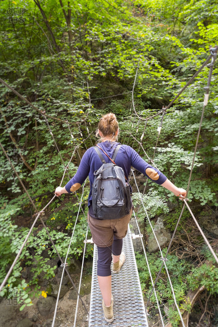 Hiker crossing metal suspension bridge on hiking trail.