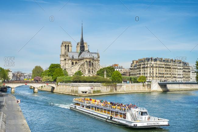 France, �le-de-France, Paris - April 7, 2014: Tourist boat passing in front of Notre Dame Cathedral on Seine River