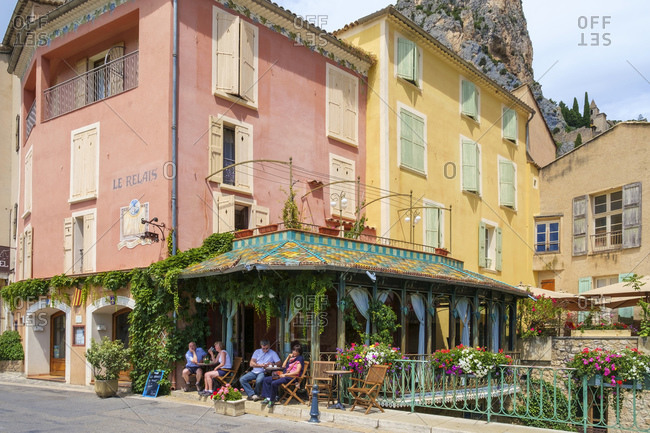 France, Provence-Alpes-Cote d'Azur, Moustiers-Sainte-Marie - July 10, 2014: People sitting outside at a cafterrace in Moustiers-Sainte-Marie