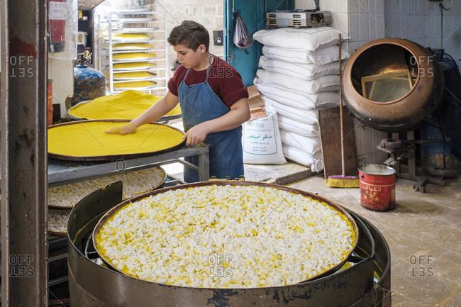 Palestine, West Bank, Nablus - March 23, 2019: Boy preparing Knafeh at al-Aqsa Sweets, Nablus, West Bank, Palestine
