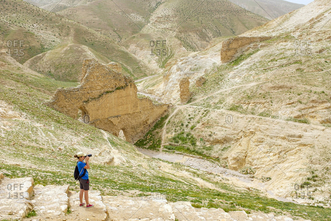 Hiker taking photos in front of Ruins of ancient aqueduct in Wadi Quelt, Jericho