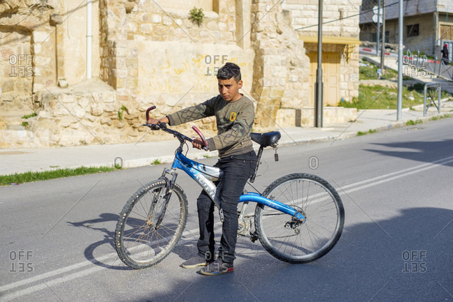 Palestine, West Bank, Hebron - April 5, 2019: Young Palestinian boy on his bicycle, Hebron (al-Khalil), West Bank, Palestine