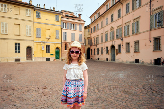 Cute child standing on medieval square in Tuscany