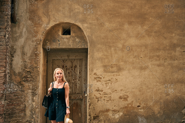 Modern female standing by old door with square hole